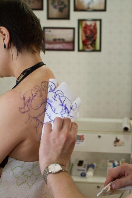 Мастер переносит рисунок на кожу