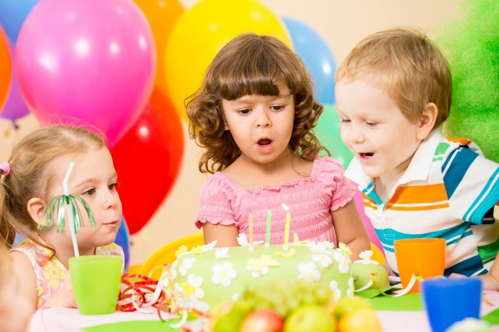 Именинница задувает свечи на торте