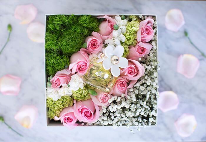 Идеальное решение для весеннего подарка: благоухающие розы в шляпной коробке с зеленью, гипсофилой и живой травой для декорирования.