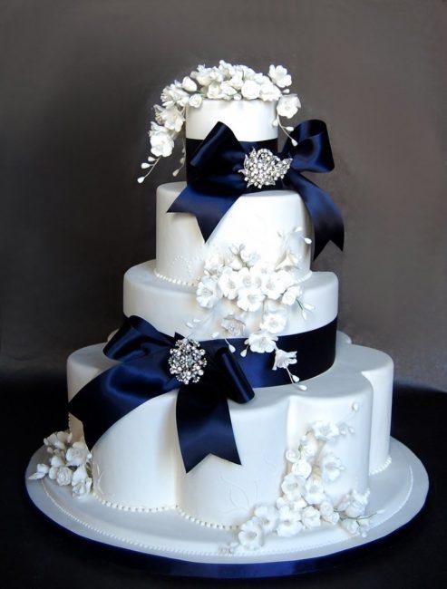 Белый свадебный торт с цветами и бантами