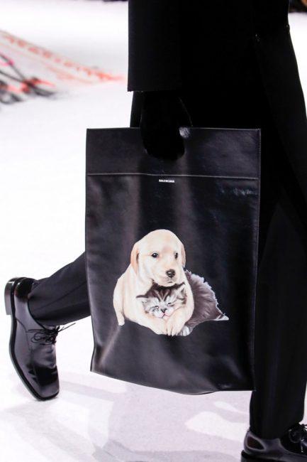 Черный total-look разбавляет черная сумка со щенками