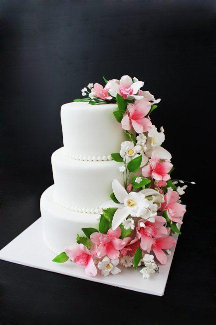 Свадебный торт, украшенный искусственными цветами