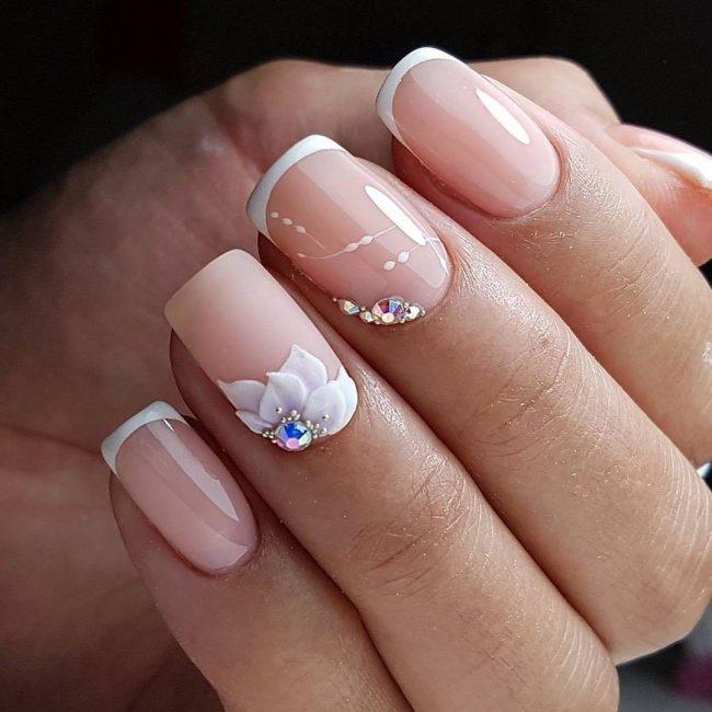 На фото представлен узор, выполненный на ногтях с французским маникюром и дополненный украшениями